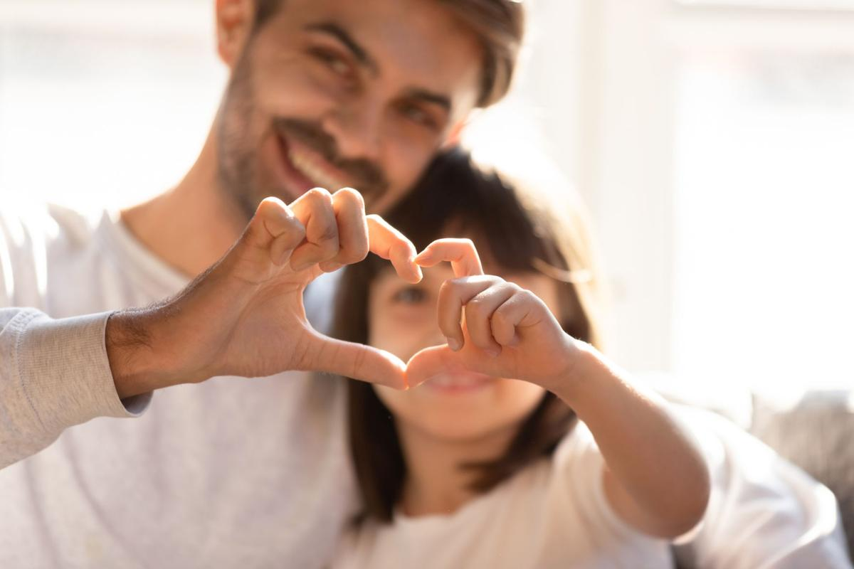 Happy young dad and little daughter make heart hand gesture