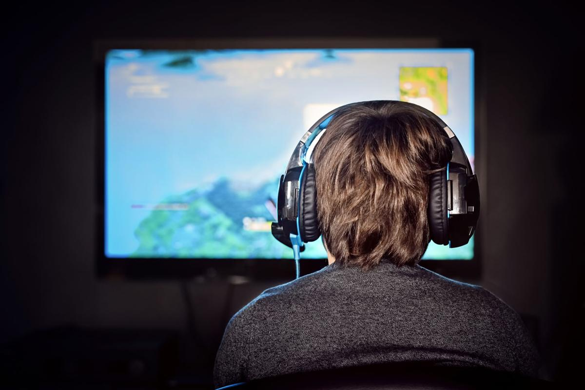 Caucasian little gamer boy wearing a headset plays video game. Video game addiction.