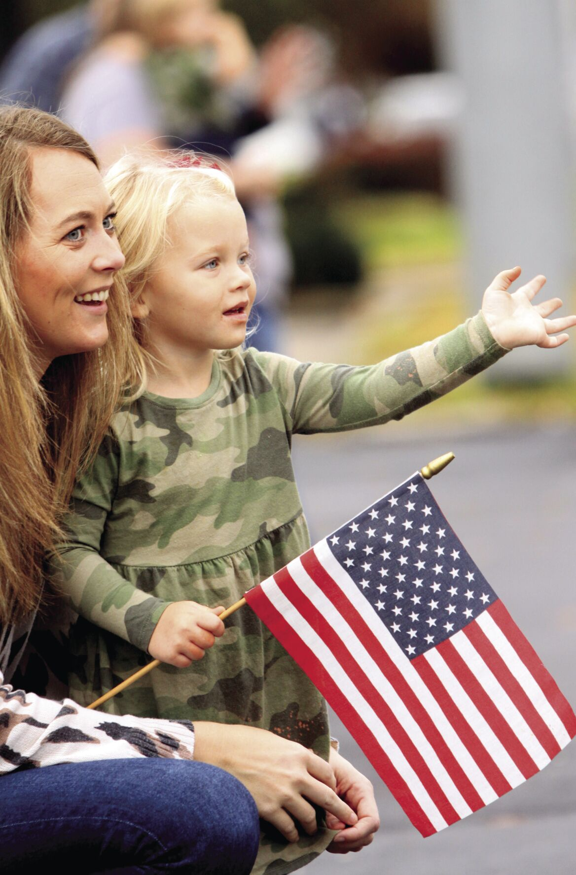 Lydia Williams, 2, gives a wave while watching the Wilson County Veterans Day Parade with her mom, Lisa, on West Main Street. The youngster is dressed in her camo for the event.