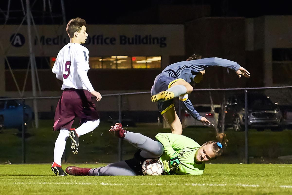 East Robertson goalie Jalen Bravo makes a save as Merrol Hyde's David Withrow trips over him while attempting to score a goal during Tuesday's game.jpg