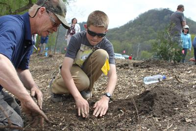 City of Winona Tree Crew member Keith Loth (left) showed Dylan Russert (center) how to plant a tree at Earth Day 2016.