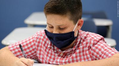 student wearing a mask in school mgn