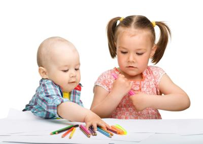 Two children are drawing on paper using markers