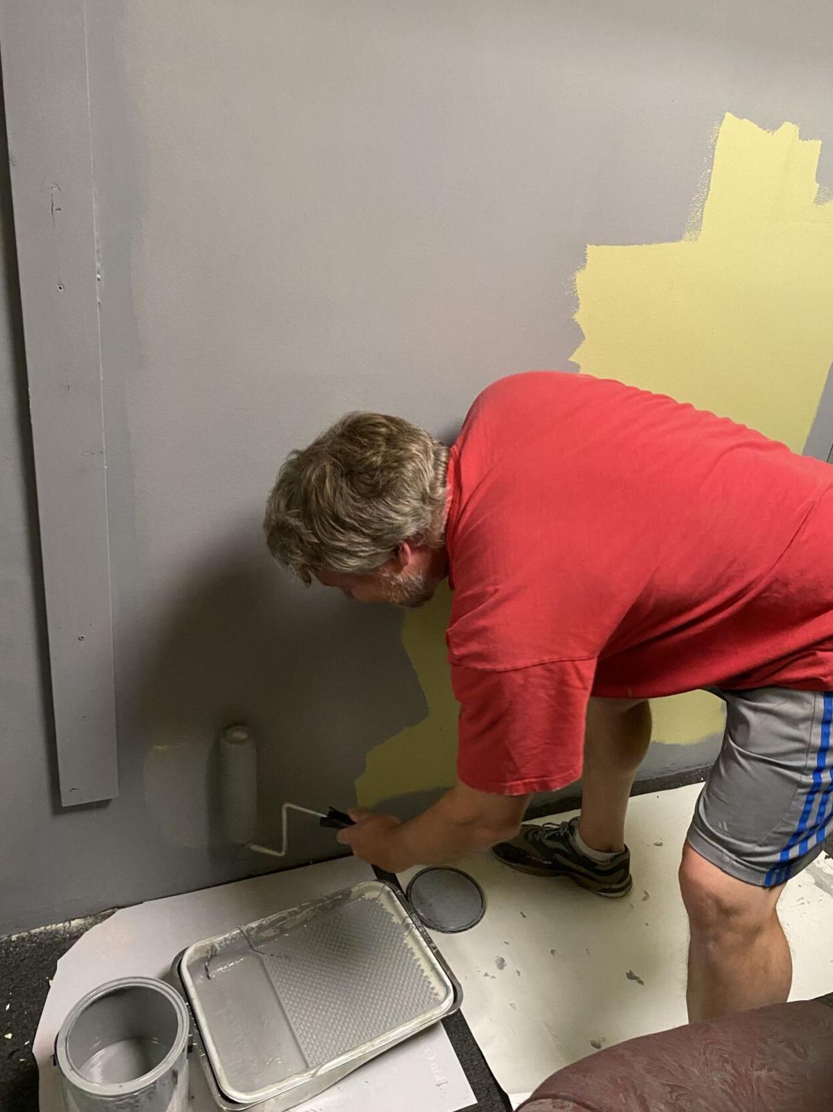 An Unsung Hero - WTC veteran and volunteer_ Michael Meeks_ paints a dressing room wall_CreditWarehouseTheatre.jpg
