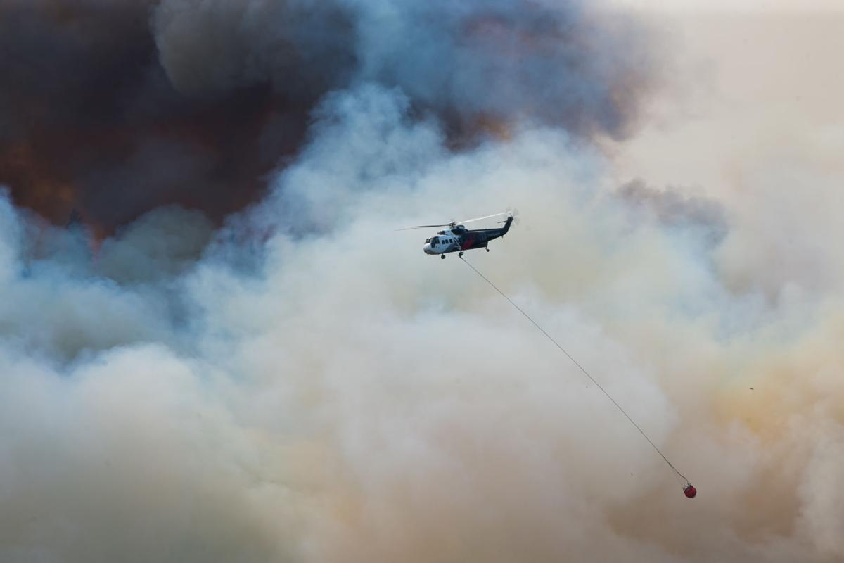 A helicopter drops water on the Schneider Springs Fire Thursday