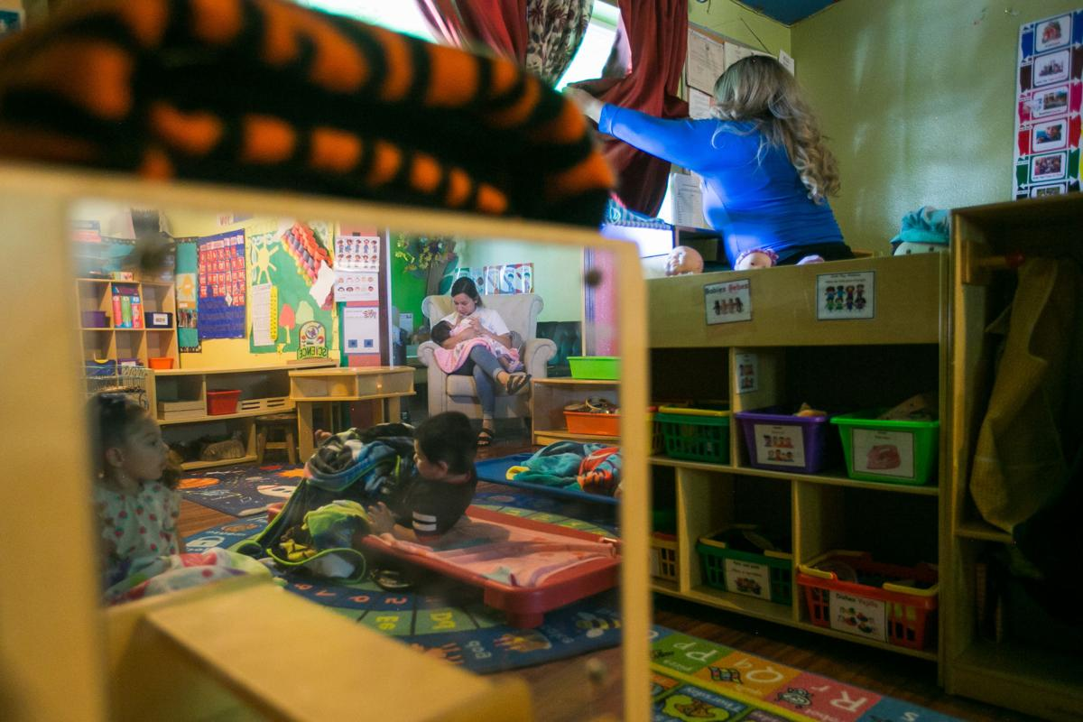 In a day care center room with green walls and cubbies, children are laying down on bright-colored cots for nap time.