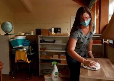 Elementary assistant Sarah Cohrs cleans the classroom at Blossoming Hill Montessori in Maple Valley.