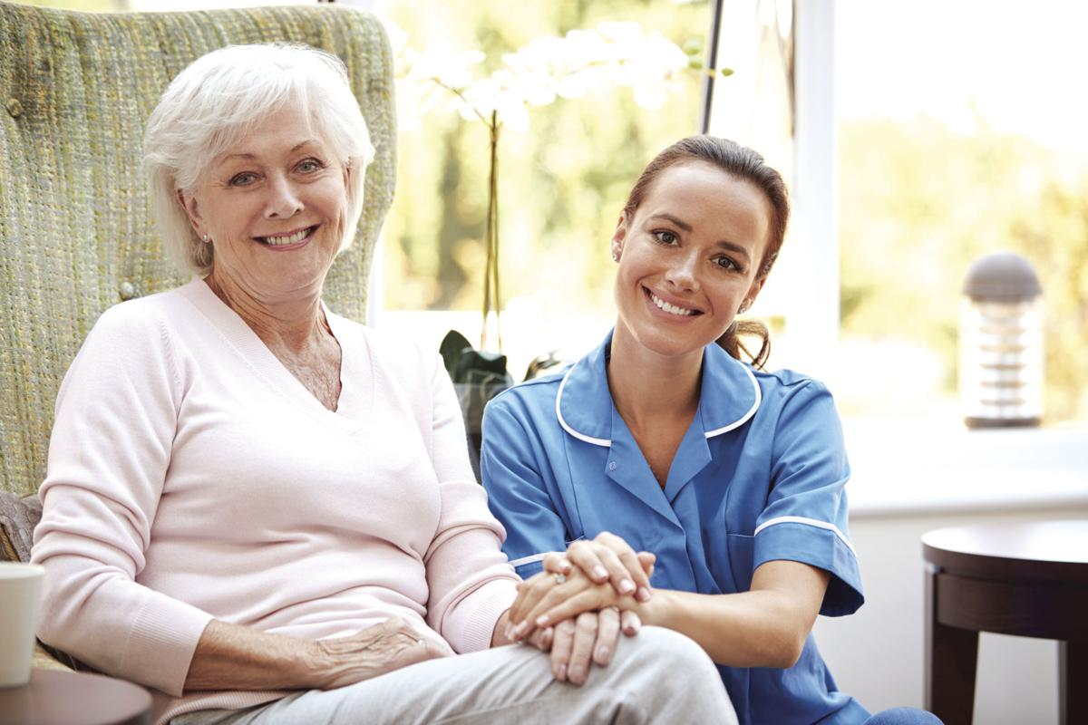 Portrait Of Senior Woman Sitting In Chair With Nurse In Retirement Home