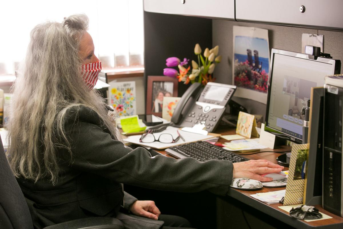 A person with long gray hair sits at a computer desk, with a bright window in the background.