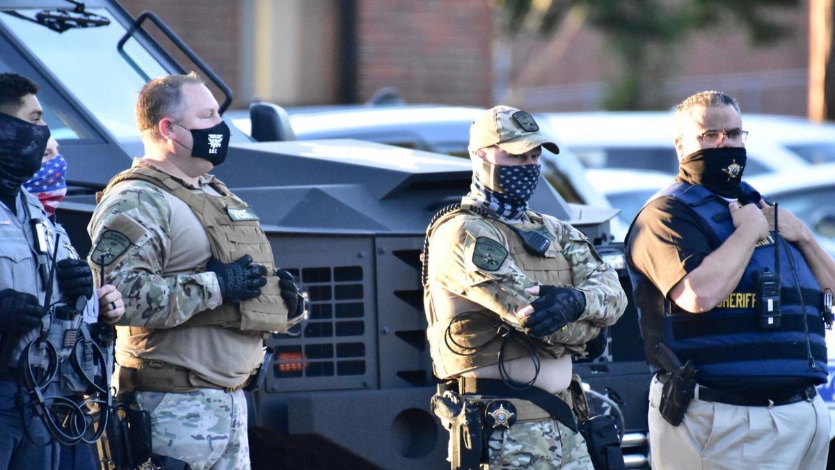 COVER-Alamance County sheriffs with armored vehicle protecting monument at Sept 2020 marcy by Tony Crider.jpg