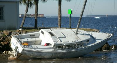 Boat aground at Punta Gorda Boat Club after dragging anchor and slamming into rocks