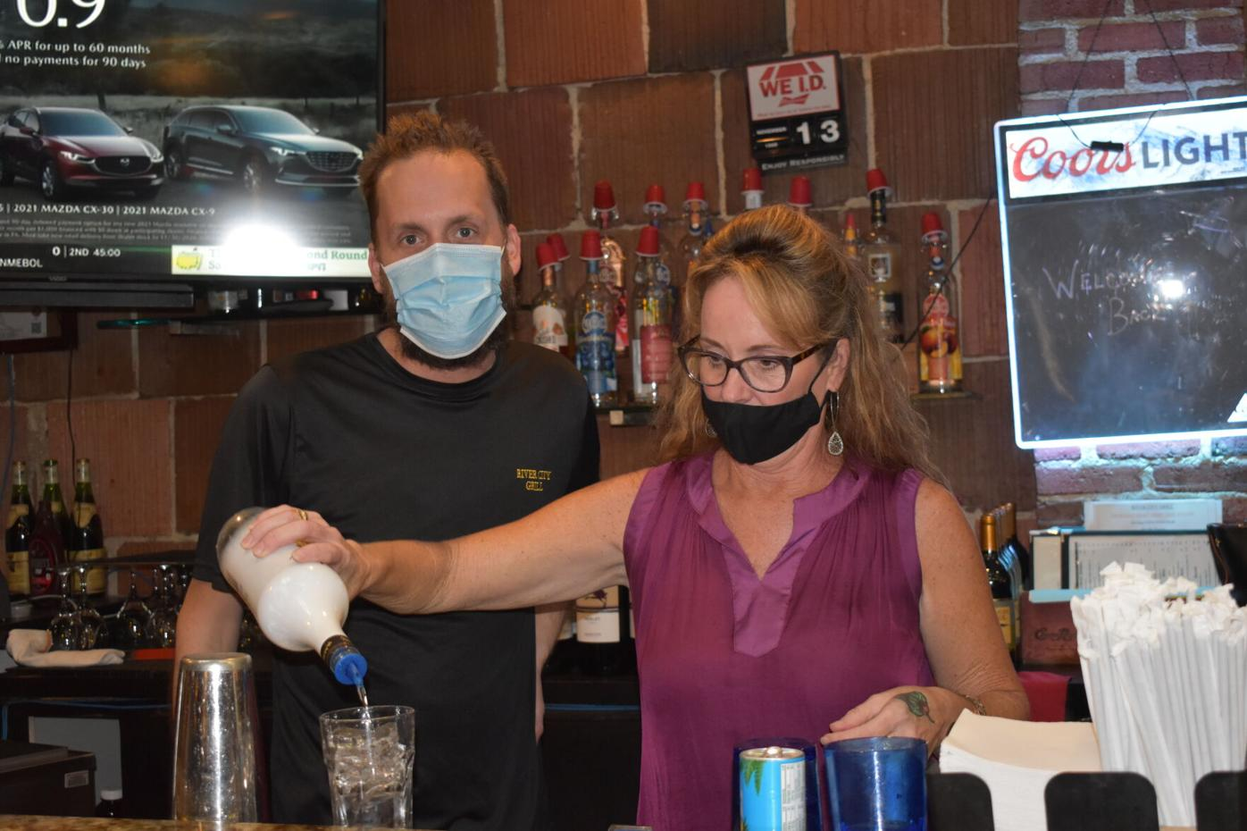 Drew Owens and Amanda Dalton mix drinks at River City Grill