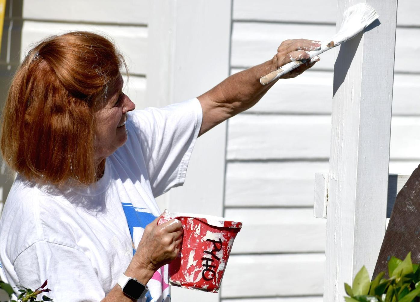 Volunteers paint historic Cigar Cottage at History Park