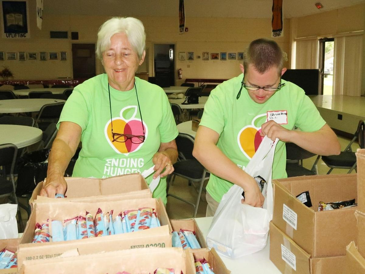 Carole and Chris Gray fill food bags for the indigent