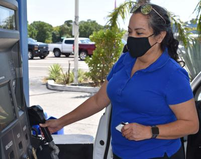 Denise Daugherty checks one of the area's lowest gasoline prices at a Marathon station