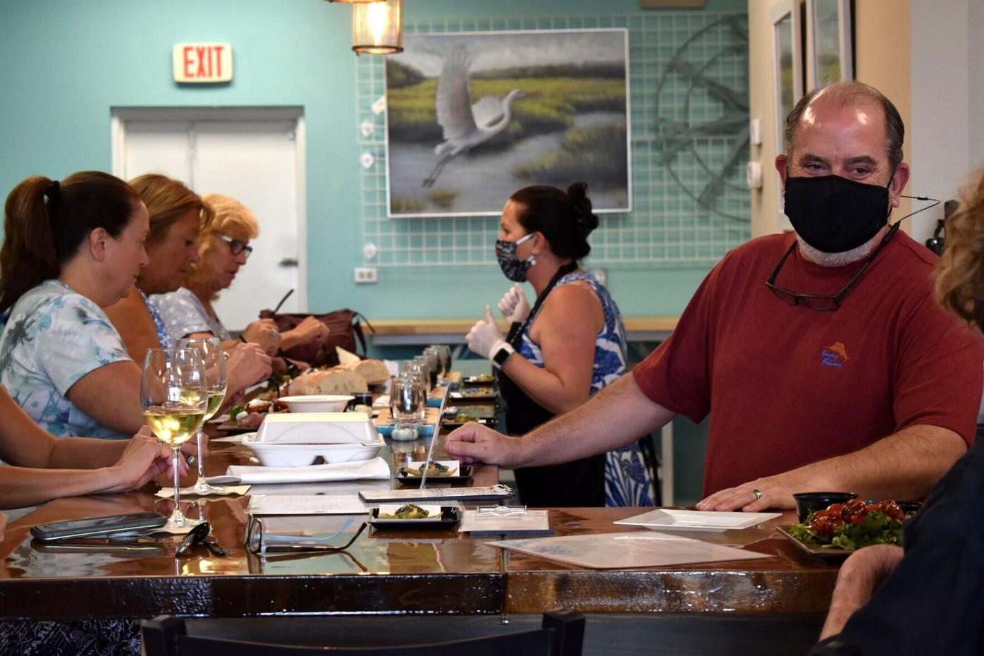 Lori and Tim Sandage, owners of Coastal Expressions & Wine, serve customers at their wine bar