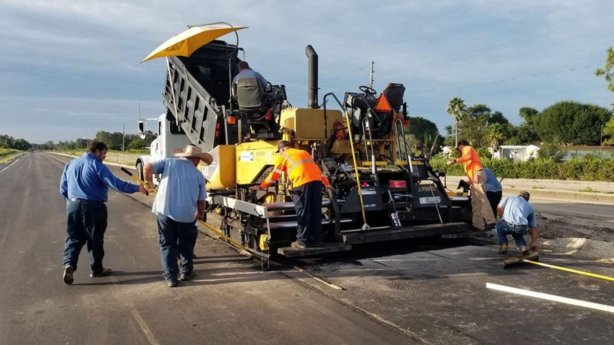Laying a first layer of asphalt